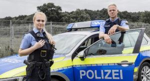 Polizisten aus Hessen vor Streifenwagen