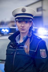 Polizistin Rheinland-Pfalz vor Streifenwagen