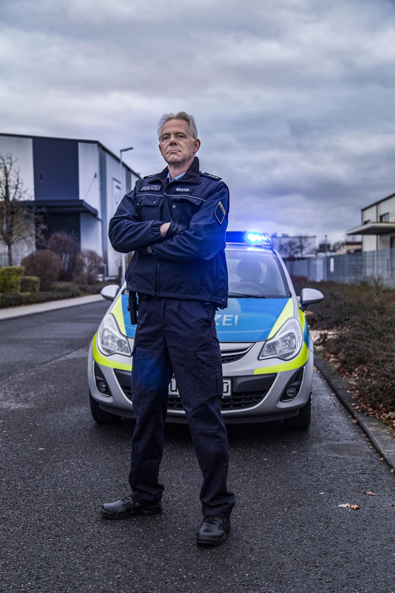 Hessischer Polizist vor Streifenwagen