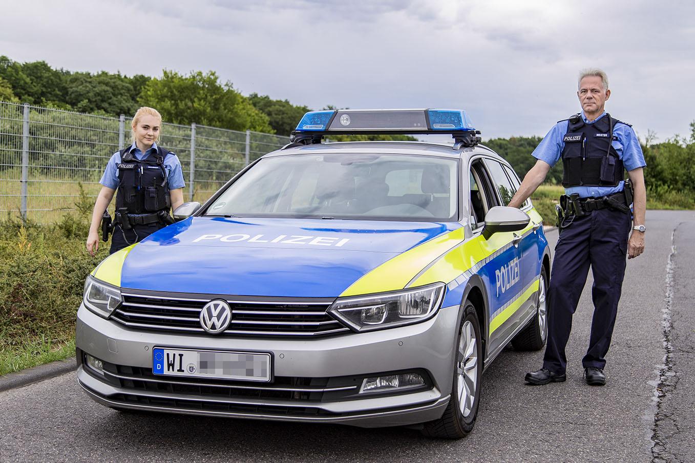 Polizisten stehen bei Streifenwagen