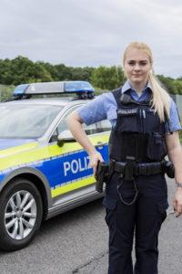 Polizistin mit Streifenwagen